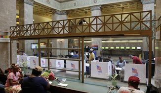 A line of voting booths are seen though glass past library patrons as people cast their votes inside the Enoch Pratt Free Library in Baltimore, Tuesday, April 26, 2016. Maryland voters have many choices and deeper impact than in recent elections as they make their choices about who should run for president and pick candidates for an open U.S. Senate seat. (AP Photo/Patrick Semansky)