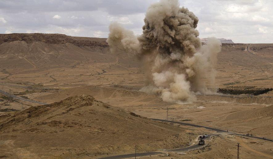 In this Thursday, April 14, 2016 photo, Smoke rises above a controlled land mine, which was detonated by Russian experts, in the ancient town of Palmyra in the central Homs province, Syria. Cluster munitions, land mines, and other unexploded ordinances are killing Syria's civil defense volunteers as they work to make battle-torn areas safe for civilians to return. (AP Photo/Hassan Ammar)