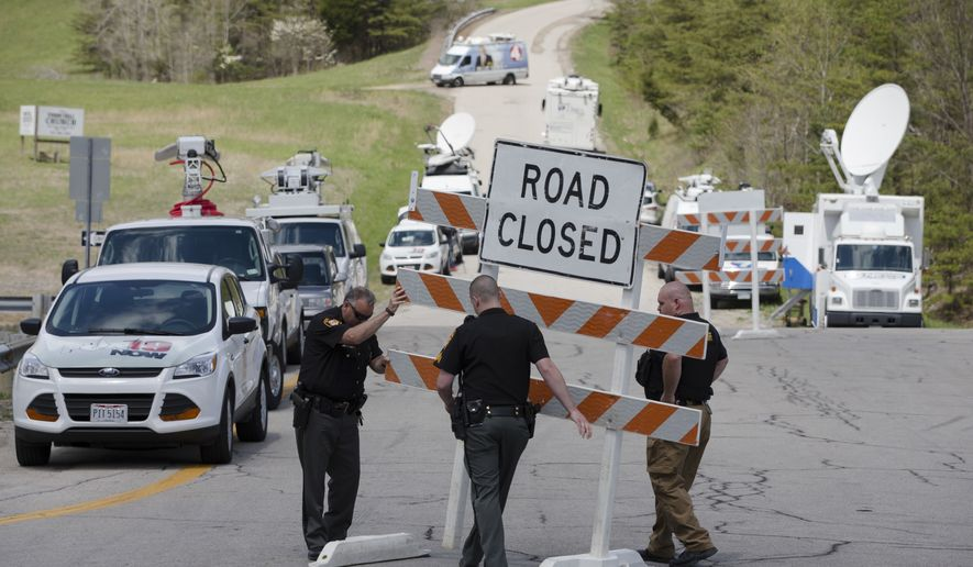 In this Friday, April 22, 2016 file photo, authorities set up road blocks at the intersection of Union Hill Road and Route 32 at the perimeter of a crime scene, in Pike County, Ohio. (AP Photo/John Minchillo, File)
