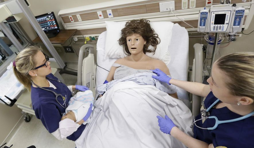 In a photo from, Monday, March 28, 2016, in Ann Arbor, Mich., nursing school students Sarah Hampel, left, and Alexandra Noga interact with a mannequin to learn how to respond to real-life medical situations, including emergencies. The high-fidelity mannequins reside in six simulation rooms set up inside the Ann Arbor school's new Clinical Learning Center. They can bleed, vomit and give birth,  just like real patients. (AP Photo/Carlos Osorio)