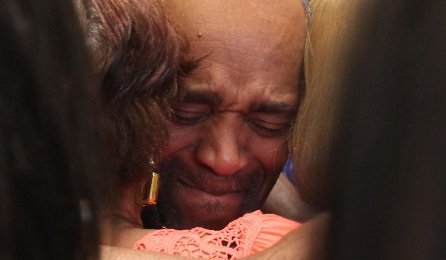 In this photo taken Monday, April 25, 2016, Darryl Pinkins is embraced by family in the lobby of the Lake County Jail in Crown Pointe, Ind., after he was released after serving more than two decades in prison for a gang rape in which he was recently cleared. (Tony V. Martin/The Times via AP)  MANDATORY CREDIT; CHICAGO LOCALS OUT;  GARY OUT