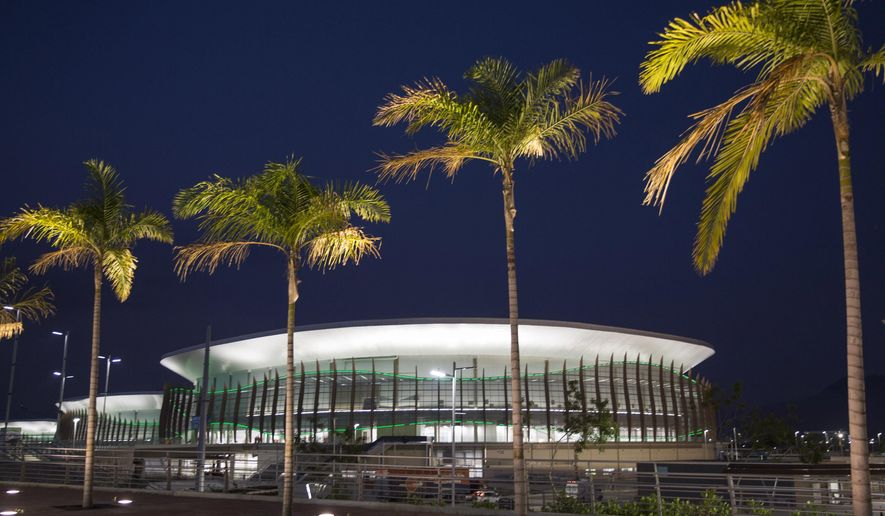 This April 11, 2016 photo shows Carioca Arena 1 behind palm trees inside Rio 2016 Olympic Park in Rio de Janeiro, Brazil. The arena will host Olympic basketball matches. Problems still hang over South America's first games. Brazil President Dilma Rousseff is being impeached and is likely to be suspended when the games open Aug. 5, partly fallout from Brazil's worst recession in decades, 10-percent unemployment, and a $3 billion Petrobras corruption scandal. Away from politics, the Zika virus threatens athletes and tourists. (AP Photo/Felipe Dana)