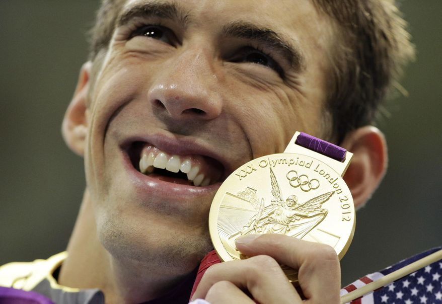 FILE - In this July 31, 2012 file photo, United States' Michael Phelps poses with his gold medal for the men's 4x200-meter freestyle relay swimming final at the Aquatics Centre in the Olympic Park during the 2012 Summer Olympics in London. If the Rio de Janeiro Olympics were held today, the United States would win the most medals and the most gold medals. And American swimmer Michael Phelps would collect five more gold medals and a bronze, bringing his overall total to 28 with a career gold-medal haul to 23. (AP Photo/Matt Slocum, File)