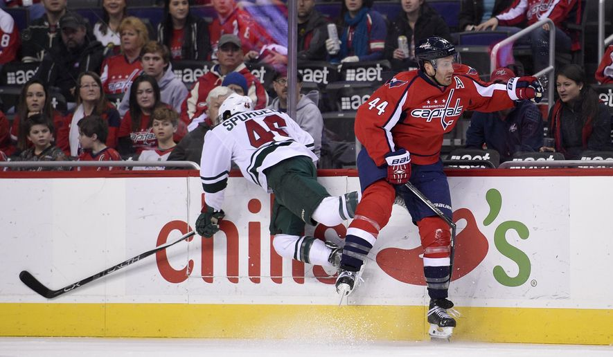 In this photo taken Feb. 26, 2016, Washington Capitals defenseman Brooks Orpik (44) and Minnesota Wild defenseman Jared Spurgeon (46) collide against the boards during the first period of an NHL hockey game in Washington. The Washington Capitals' only major injury in the first round was to defenseman Brooks Orpik. As they prepare to face Orpik's former team, the Pittsburgh Penguins, his status is uncertain. He makes a major impact. (AP Photo/Nick Wass)