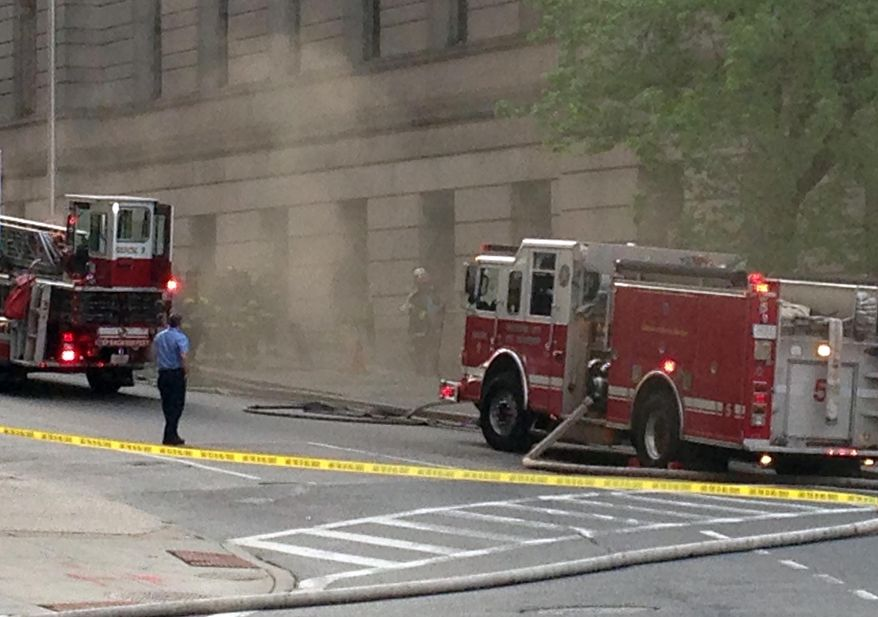 Emergency personal respond to a fire in the Mitchell Courthouse in downtown Baltimore, which forced evacuation of the building Tuesday, April 26, 2016. Fire Department spokesman Capt. Roman Clark said by phone that what little fire that was outside the west building was quickly extinguished. (AP Photo/Brian Witte)