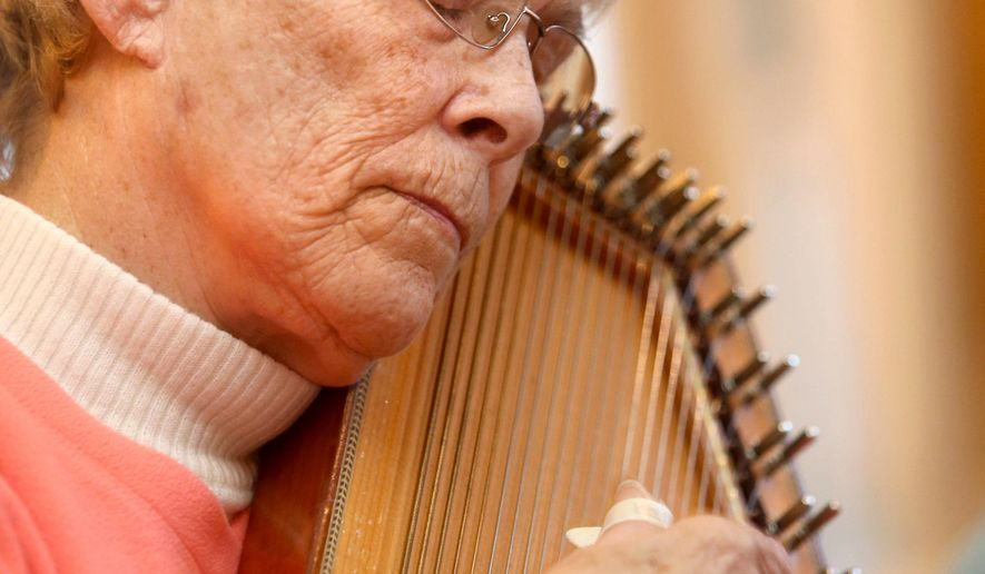 In this photo taken April 8, 2016, Verla Boyd closes her eyes as she strums her autoharp along with the Hoosier String Players, a folk and mountain music club, while they jam together in Kokomo, Ind. The group has been playing together for about 16 years. (Kelly Lafferty Gerber/The Kokomo Tribune via AP) MANDATORY CREDIT