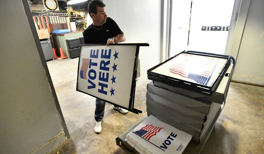 "Dusty DeVinney places ""vote here"" signs onto a cart as he loads election materials at the Willowbank building Monday, April 25,2016, in Bellefonte, Pa., in preparation for Tuesday's primary election. For the first time in many years, Democrats and Republicans in Pennsylvania on Tuesday pick presidential candidates in a meaningful primary. A U.S. Senate primary will determine who represents the Democrats this fall in the race to unseat Sen. Pat Toomey, and voters from both parties choose their candidates for attorney general. (Nabil K. Mark/Centre Daily Times via AP) MANDATORY CREDIT; MAGS OUT"