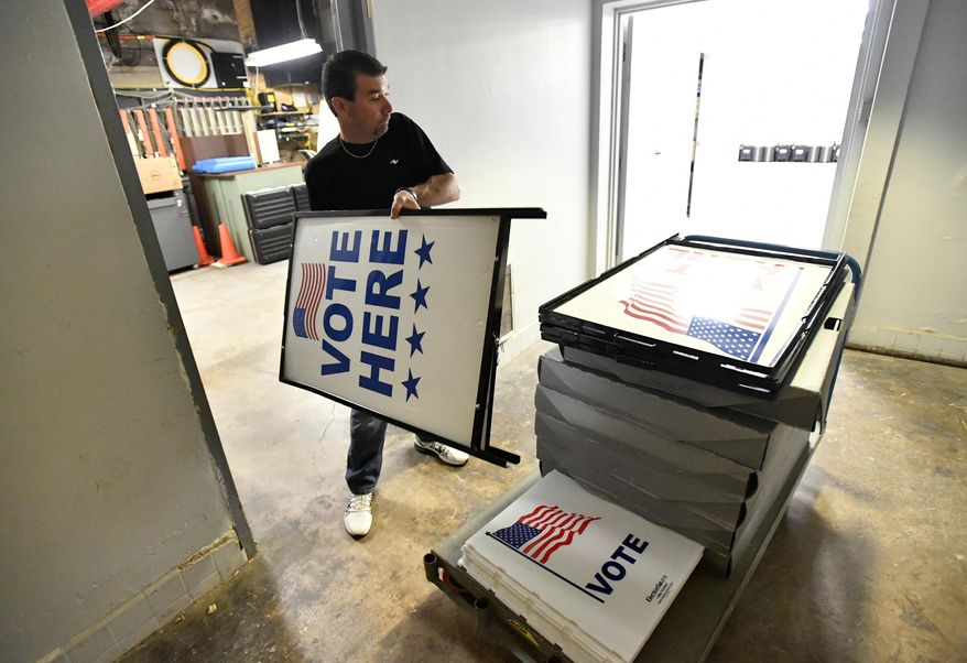 """Dusty DeVinney places """"vote here"""" signs onto a cart as he loads election materials at the Willowbank building Monday, April 25,2016, in Bellefonte, Pa., in preparation for Tuesday's primary election. For the first time in many years, Democrats and Republicans in Pennsylvania on Tuesday pick presidential candidates in a meaningful primary. A U.S. Senate primary will determine who represents the Democrats this fall in the race to unseat Sen. Pat Toomey, and voters from both parties choose their candidates for attorney general. (Nabil K. Mark/Centre Daily Times via AP) MANDATORY CREDIT; MAGS OUT"""