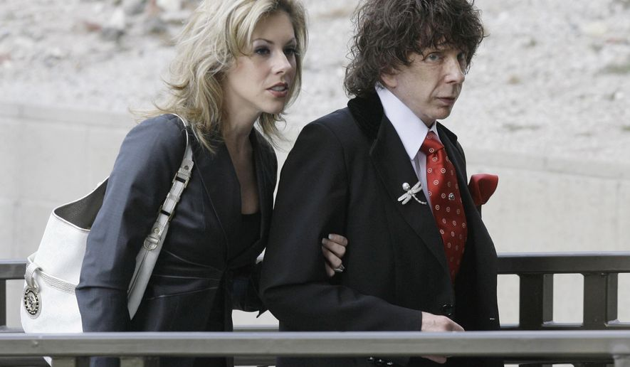 """FILE - In this March 28, 2008 file photo, music producer Phil Spector and his wife Rachelle Spector, arrive at the Los Angeles County Superior Court for a discovery hearing in downtown Los Angeles. An attorney for Spector's wife Rachelle wrote in a statement issued Tuesday, April 26, 2016, that the producer's divorce filing is """"heartbreakingly bizarre"""" and that she has been a devoted wife who has given him the best possible care while he is imprisoned for the shooting death of actress Lana Clarkson. (AP Photo/Nick Ut, File)"""
