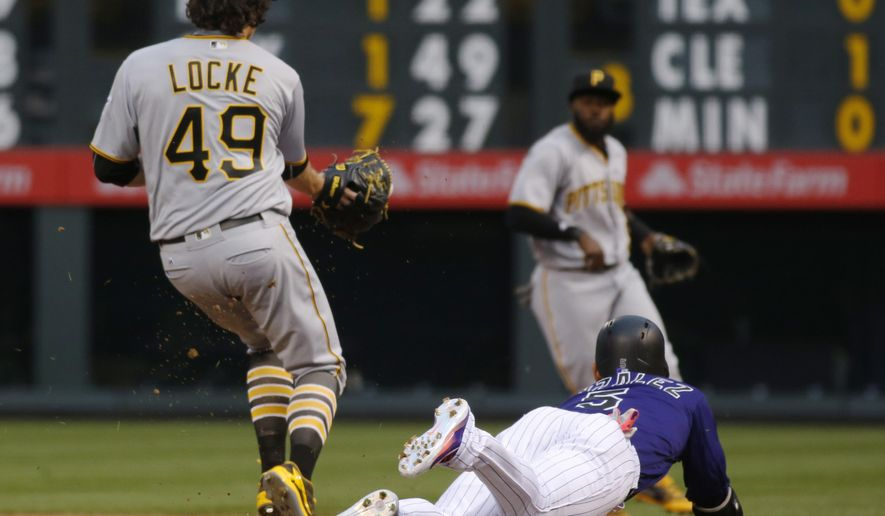 Colorado Rockies' Carlos Gonzalez, front right, dives safely into first base for an infield single as Pittsburgh Pirates starting pitcher Jeff Locke, front left, fields the throw from second baseman Josh Harrison in the first inning of a baseball game Monday, April 25, 2016, in Denver. (AP Photo/David Zalubowski)