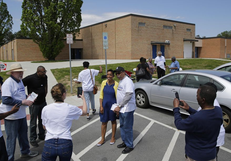Rep. Donna Edwards, D-Md., center in blue and yellow, poses for a photo as she greets voters and volunteers outside a polling place at Winfield Elementary School in Windsor Mill, Md., Tuesday, April 26, 2016. Edwards is running against Rep. Chris Van Hollen, D-Md., in the Democratic primary for U.S. Senate. (AP Photo/Patrick Semansky)