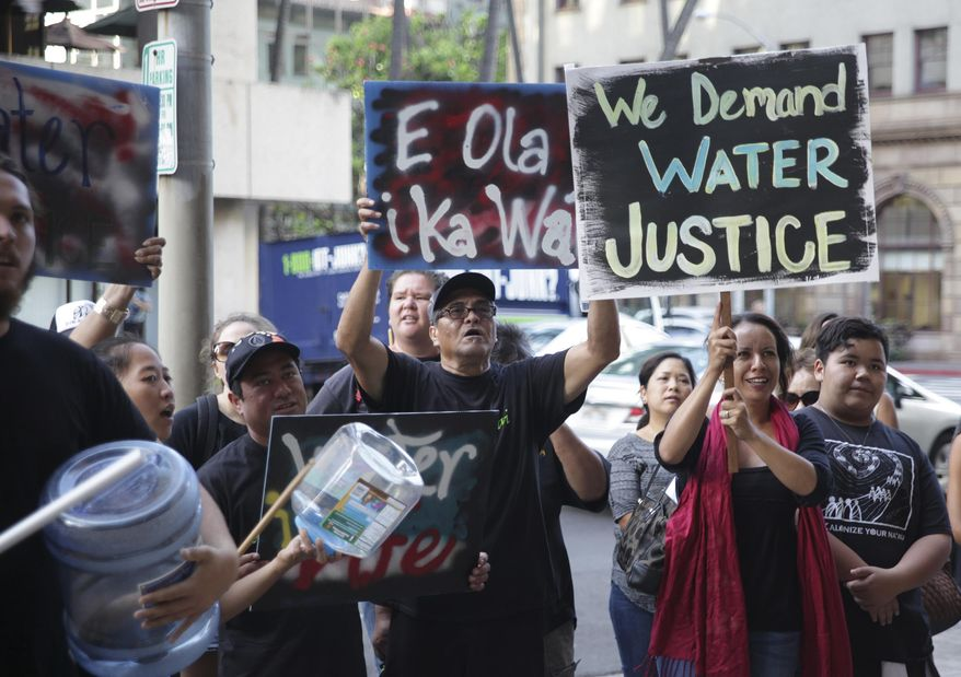 Protesters against a bill to allow companies and other water-rights holders to continue diverting water from Maui streams hold a rally outside of the Alexander & Baldwin Building in Honolulu, Tuesday, April 26, 2016. With Alexander & Baldwin scheduled to stop sugar operations at the end of the year, opponents say the company is just trying to hold onto water rights while it sucks the island dry of a public resource that many hope will be used to restore dry stream beds and farming communities. (AP Photo/Marina Riker)