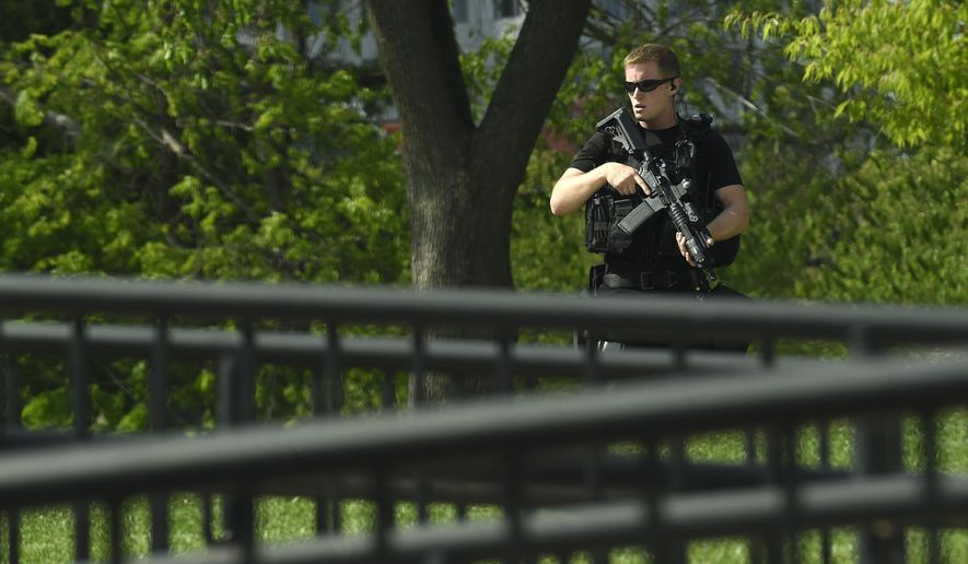 A uniformed Secret Service agent patrols the North Lawn of the White House in Washington, Tuesday, April 26, 2016. A man fleeing a robbery jumped a fence at the White House complex and was arrested, the Secret Service said, triggering a brief lockdown at the presidential residence. Secret Service officers arrested the man after he jumped the fence alongside the Eisenhower Executive Office Building, which is part of the White House complex.(AP Photo/Susan Walsh)