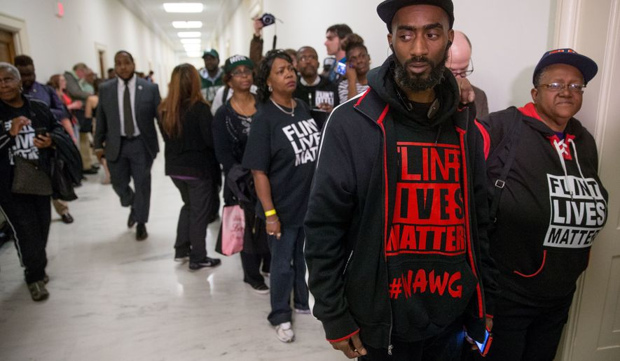 """Flint, Mich., residents and supporters wear shirts that reads """"Flint Lives Matter"""" as they wait outside a committee hearing on the Flint water crisis in Washington on March 17, 2016. In proposing a tougher limit for lead in drinking water, Gov. Rick Snyder wants to lift Michigan from the depths of the Flint crisis to being a model for water safety that can help assess whether the current national rules governing lead are too lax. (Associated Press) **FILE**"""