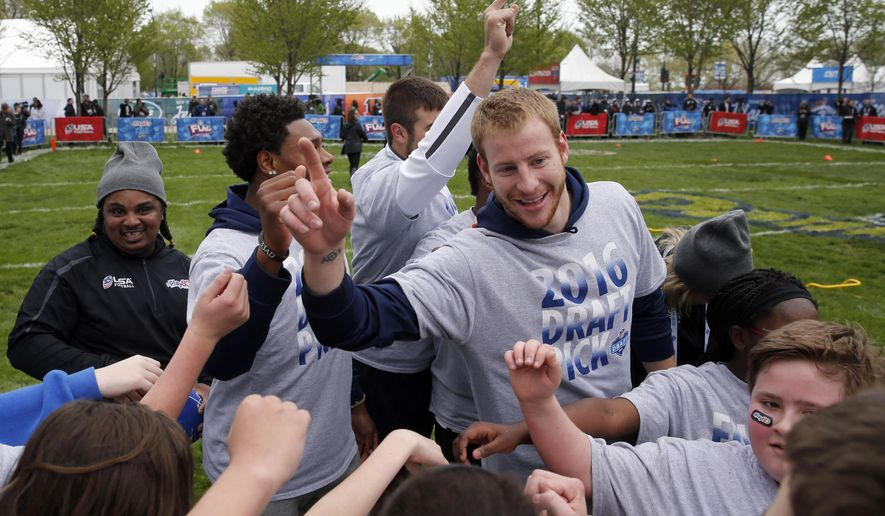 North Dakota State's Carson Wentz huddles with children during an NFL Play 60 event at Grant Park, Wednesday, April 27, 2016, in Chicago before Thursday's first round of the NFL football draft. (AP Photo/Kiichiro Sato)