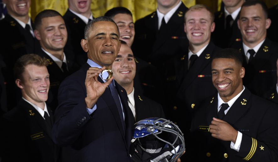 President Barack Obama holds up a ring that was presented to him by the United States Naval Academy Football Team in the East Room of the White House in Washington, Wednesday, April 27, 2016, during a ceremony to present the team with the 2015 Commander-in-Chief's Trophy. Navy quarterback Keenan Reynolds watches, front right. (AP Photo/Susan Walsh)