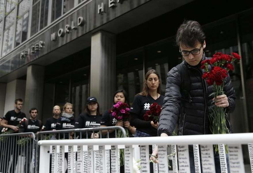 Activists line up to put flowers in crib in front of Pfizer world headquarters in New York, Wednesday, April 27, 2016. The crib filled with flowers, organized by Doctors Without Borders, was delivered to Pfizer with a petition demanding that the pharmaceutical company lower the cost of the pneumonia vaccine.   (AP Photo/Seth Wenig)