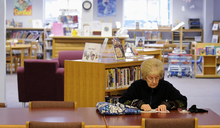 In this April 7, 2016 photo, Gloria Kizora reads inside the Manteno Public Library in Manteno, Ill., while waiting for her ride home. Libraries might have swapped card catalogs for computer kiosks a long time ago and faced the unprecedented explosion of information on the Internet. But the digital age still hasn't changed one truth about them _ people visit them to check out books. (Mike Voss/The Daily Journal via AP)  MANDATORY CREDIT