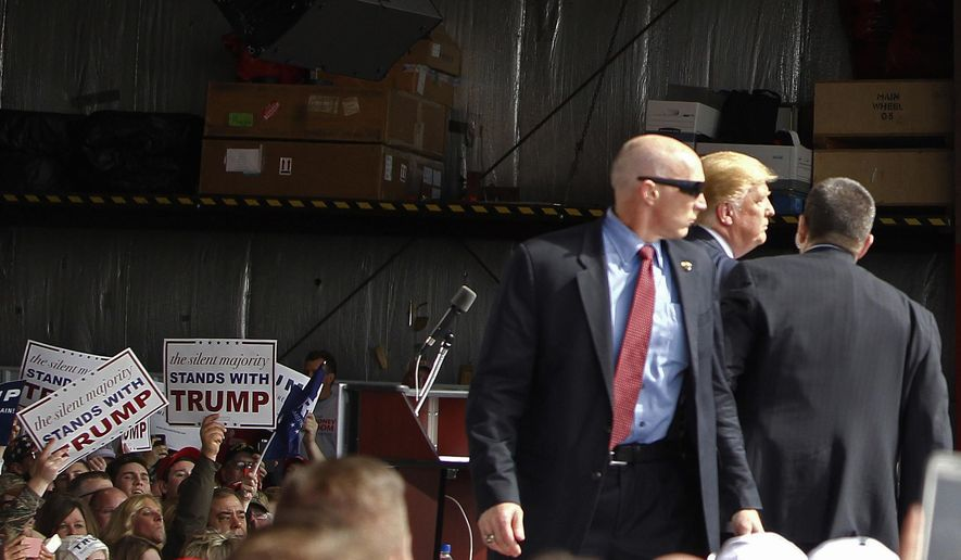 FILE - In this March 12, 2016, file photo, Secret Service agents guard Republican presidential candidate Donald Trump after a man rushed the stage during a campaign rally at the Wright Brothers Aero Hangar at Dayton International Airport in Vandalia, Ohio. Thomas DiMassimo, a 22-year-old Wright State University student, has pleaded not guilty to a misdemeanor charge of illegally entering a restricted area. During a Wednesday, April 27, 2016, status conference, participants told Magistrate Sharon Ovington that no agreement has been reached yet to avoid a trial scheduled May 31, 2016. (AP Photo/Kiichiro Sato, File)
