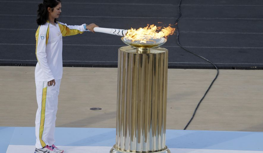 Rowing World Champion Katerina Nikolaidou of Greece lights the cauldron during the handover ceremony for the Olympic Flame at Panathinean stadium in Athens, Wednesday, April 27, 2016. The flame arrives in Brazil on May 3, and will be relayed across the vast country by about 12,000 torchbearers before the Aug. 5 opening ceremony in Rio de Janeiro's Maracana Stadium. (AP Photo/Thanassis Stavrakis)