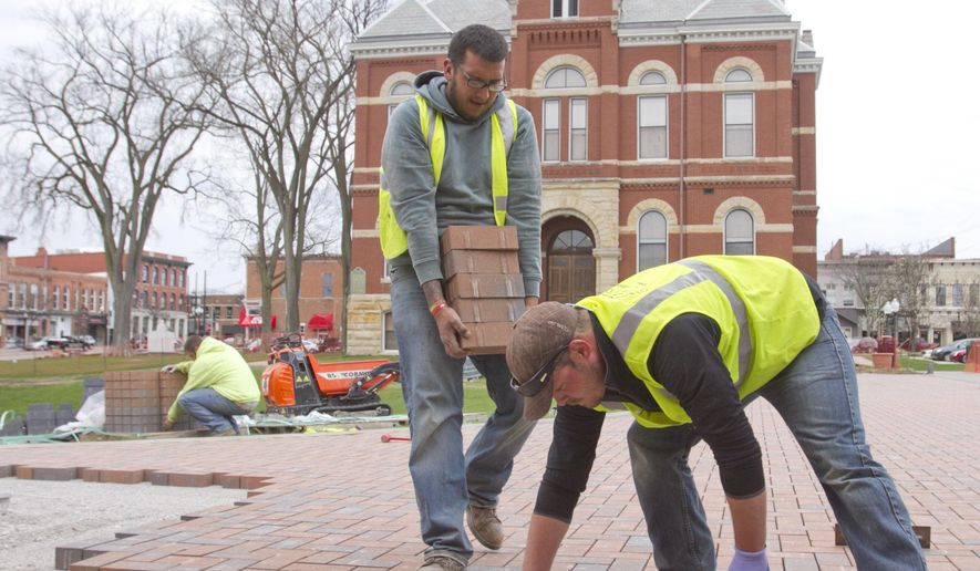 In a Tuesday, April 19, 2016 photo, Ryan Parlove places bricks in the Historic Livingston County Courthouse amphiteater while Chris Juarez keeps the supply coming and Cody Watkins unloads a new pallet of bricks. The Evergreen Outdoor employees will install over 36,000 bricks between the upper area they work on here and the lower area closer to Grand River by the time the job is complete. (Gillis Benedict/Livingston Daily Press & Argus via AP)