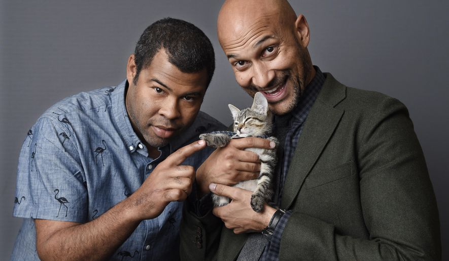"In this April 23, 2016 photo, Jordan Peele, left, and Keegan-Michael Kay hold a ten-week-old tabby as they pose for a portrait to promote their film, ""Keanu,"" at The Beverly Hilton Hotel in Beverly Hills, Calif. (Photo by Chris Pizzello/Invision/AP)"