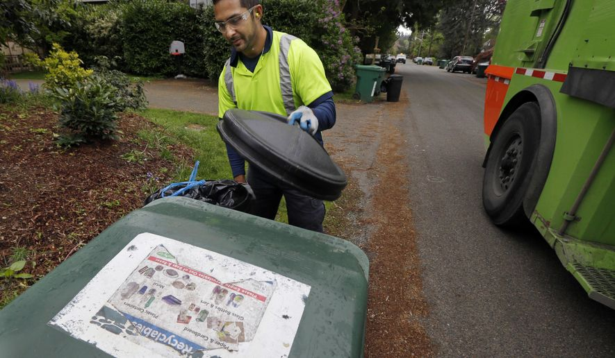 FILE - In this April 15, 2016 file photo, David Morales, a garbage driver with Recology, picks up a garbage container for Seattle Public Utilities in Seattle. A judge on Wednesday, April 27, 2016 stopped enforcement of a Seattle ordinance barring people from throwing compost in the trash, declaring it unconstitutional. The measure required trash collectors to tag garbage cans that contain more than 10 percent compostable material with education information. (AP Photo/Ted S. Warren, File)