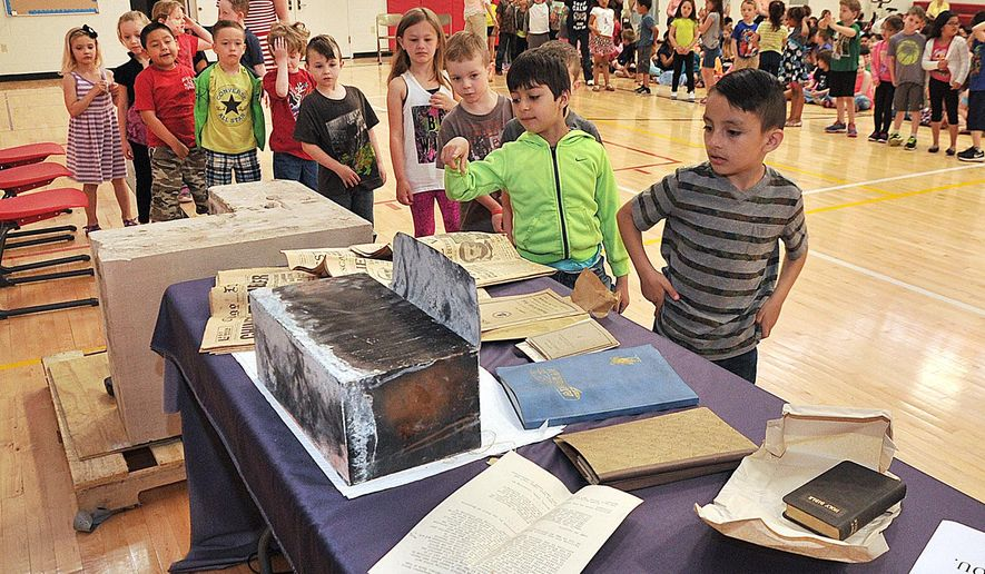 Jefferson Elementary School students file past the contents of a time capsule removed from the cornerstone at the old Jefferson Elementary School in Muscatine, Iowa, Tuesday, April 25, 2016. Items included a Bible, a phone book and three newspapers. (Beth Van Zandt/Muscatine Journal via AP)