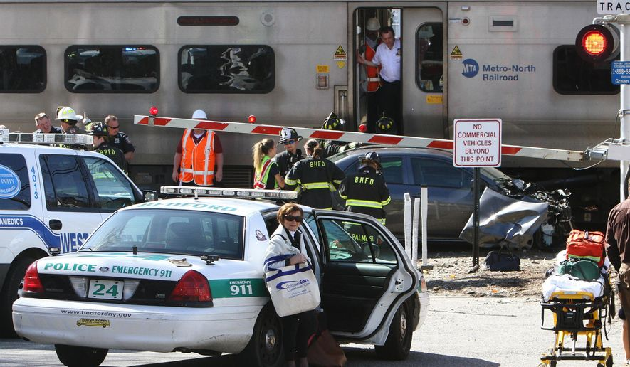 Firefighters and police officers work a collision site of a northbound Metro-North train and a vehicle in Bedford Hills, N.Y., Wednesday, April 27, 2016. Officials said the car apparently became stuck on the tracks and the driver got out before the train clipped the vehicle. (Frank Becerra Jr./The Journal News via AP) MANDATORY CREDIT