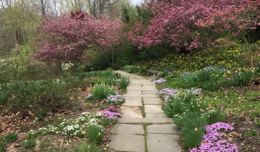This April 19, 2016 photo shows a rustic path lined with spring flowers at the Virginia B. Fairbanks Art & Nature Park, part of the Indianapolis Museum of Art campus in Indianapolis. The park's 100 acres include sculptures, swings, a lake and woodland trails. (AP Photo/Beth J. Harpaz)
