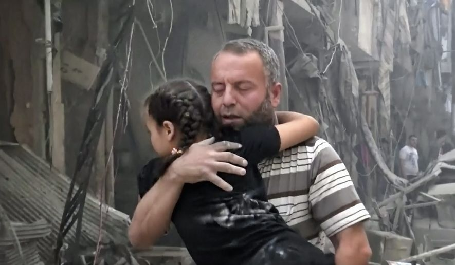 A man carries a child after airstrikes hit Aleppo, Syria, on Thursday. A Syrian monitoring group and a first-responders team say new airstrikes on the rebel-held part of the contested city of Aleppo have killed over a dozen people and brought down at least one residential building. (Associated Press)