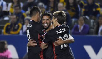 D.C. United midfielder Lamar Neagle, center, celebrates his goal with midfielder Luciano Acosta, left, and forward Chris Rolfe during the first half of an Major League Soccer match against the Los Angeles Galaxy, Sunday, March 6, 2016, in Carson, Calif. (AP Photo/Mark J. Terrill) **FILE**