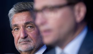 Wizards Majority Owner Ted Leonsis, left, listens as his new coach, Scott Brooks, right, answers questions during Brooks's introductory news conference at the Verizon Center in Washington, Wednesday, April 27, 2016. Brooks reached a five-year agreement with the team last week.  (AP Photo/Pablo Martinez Monsivais)