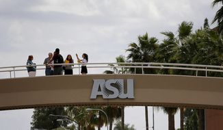 People stand on the campus overpass, Thursday, April 28, 2016, at Arizona State University in Tempe, Ariz. Arizona's republican leaders have earmarked millions of dollars in next year's proposed budget for schools at the state's public universities that are backed by billionaire Republican donor Charles Koch. (AP Photo/Matt York)