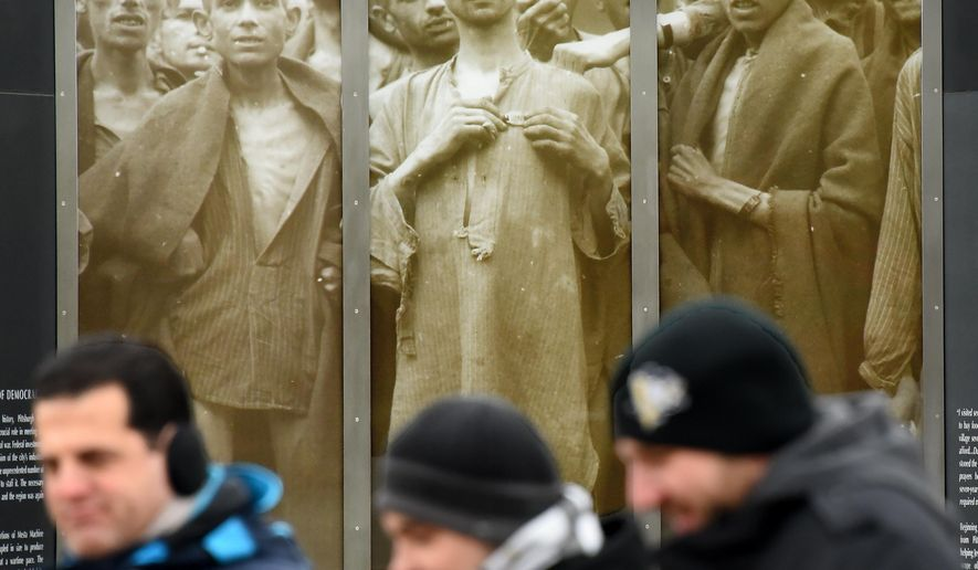 ADVANCE FOR WEEKEND EDITIONS - In this Jan. 27, 2016 photo, people walk past images of concentration camp survivors at the Southwestern Pennsylvania World War II Memorial in Pittsburgh. (Bob Donaldson/Pittsburgh Post-Gazette via AP) MANDATORY CREDIT