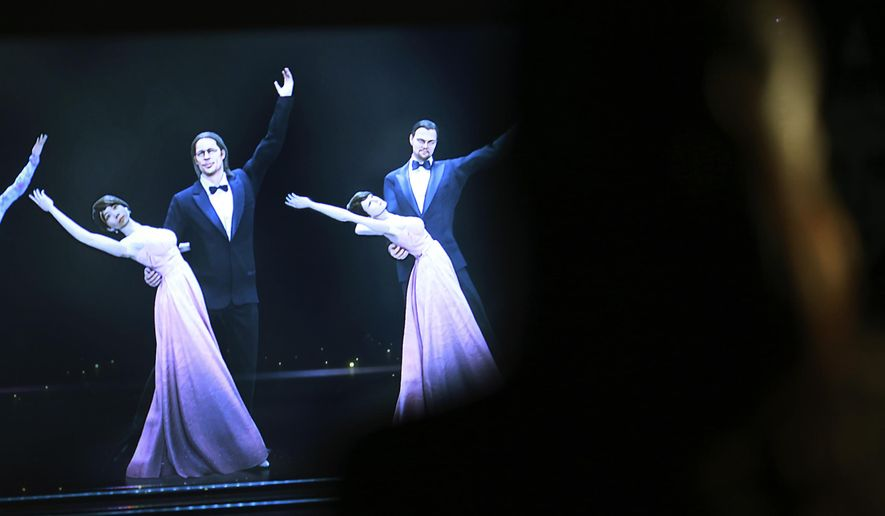 Mizuho Shinden watches the hologram of dancers with her face attached, far left, featuring actors Brad Pitt, second left, Leonardo DiCaprio, far right, at the newly opened Hologram Dance Theater at Madame Tussauds in Tokyo, Thursday, April 28, 2016. Madam Tussauds in Tokyo is launching an event allowing visitors to virtually join a 3D world where they can dance with holograms of celebrities such as Brad Pitt, Leonardo DiCaprio, and Lady Gaga. (AP Photo/Eugene Hoshiko)