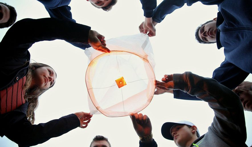 Friends and family of Tyler and Richard Smith prepare to release a lantern in their memory at Mattawan High School in Mattawan, Mich. on Wednesday, April 27, 2016.  A tree has been dedicated in memory of Richard Smith and his 17-year-old son, Tyler, two of the victims of February mass shootings in southwestern Michigan.  Uber driver Jason Dalton is charged in the apparently random Kalamazoo-area attacks that killed six.  (Chelsea Purgahn/Kalamazoo Gazette-MLive Media Group via AP) LOCAL TELEVISION OUT; LOCAL RADIO OUT; MANDATORY CREDIT