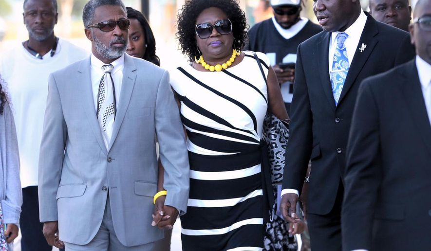 Attorney Benjamin Crump, right, talks with Clinton Jones,Sr and Katti Jones, Corey Jones' father and stepmother, as the family arrives at the Palm Beach County Courthouse Thursday,  April 28, 2016 in West Palm Beach, Fla.  Police shot Corey Jones, a legally armed musician who was waiting on the side of the road for a tow truck last October.  (Lannis Waters/Palm Beach Post via AP)  MAGS OUT; TV OUT; NO SALES; MANDATORY CREDIT