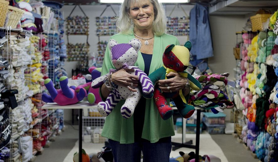 ADVANCE FOR WEEKEND EDITIONS -APRIL 30-MAY 2 - In this April 6, 2016, Jacqueline Lamont of Midland, Mich., poses for a portrait with two stuffed bears that she made in her sewing room. Lamont has sewn more than 500 bears that she gives away to law enforcement, hospitals and other agencies. Lamont's bears have brought comfort to children at MidMichigan Medical Center-Midland, Shelterhouse, children who encounter law enforcement and the St. Joseph Health System in Tawas. (Brittney Lohmiller/Midland Daily News via AP)MANDATORY CREDIT