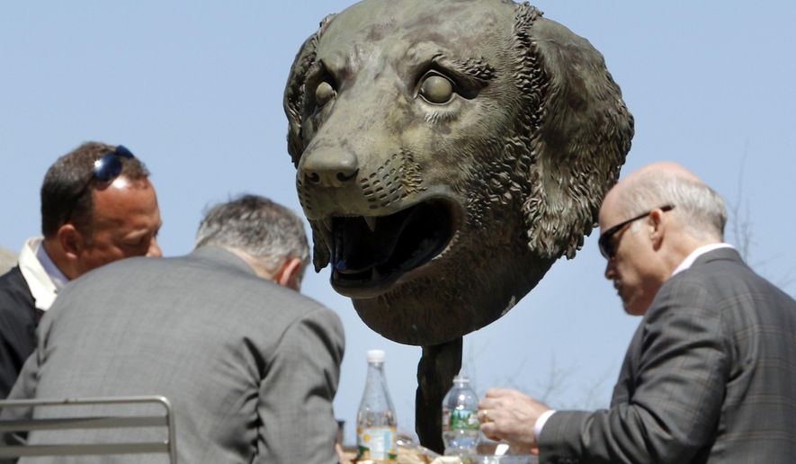 In this Wednesday, April 27, 2016 photo, one of 12 gigantic bronze animal heads representing the signs of the Zodiac by Chinese artist Ai Weiwei stands behind businessmen eating lunch on the Rose Kennedy Greenway in Boston. The sculptures are scheduled to remain on public display in the park through October. (AP Photo/Bill Sikes)