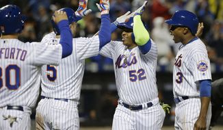 New York Mets' Yoenis Cespedes (52) is greeted by David Wright (5), Curtis Granderson (3) and Michael Conforto (30) after hitting a grand slam against the San Francisco Giants during the third inning of a baseball game, Friday, April 29, 2016, in, New York. (AP Photo/Julie Jacobson)