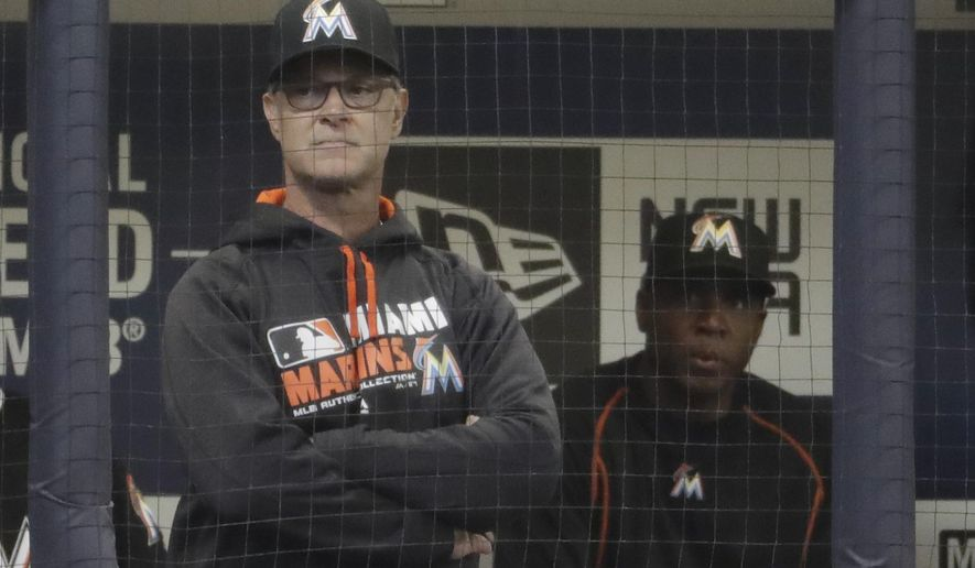 Miami Marlins manager Don Mattingly and hitting coach Barry Bonds wait for the start of a baseball game against the Milwaukee Brewers Friday, April 29, 2016, in Milwaukee. (AP Photo/Morry Gash)