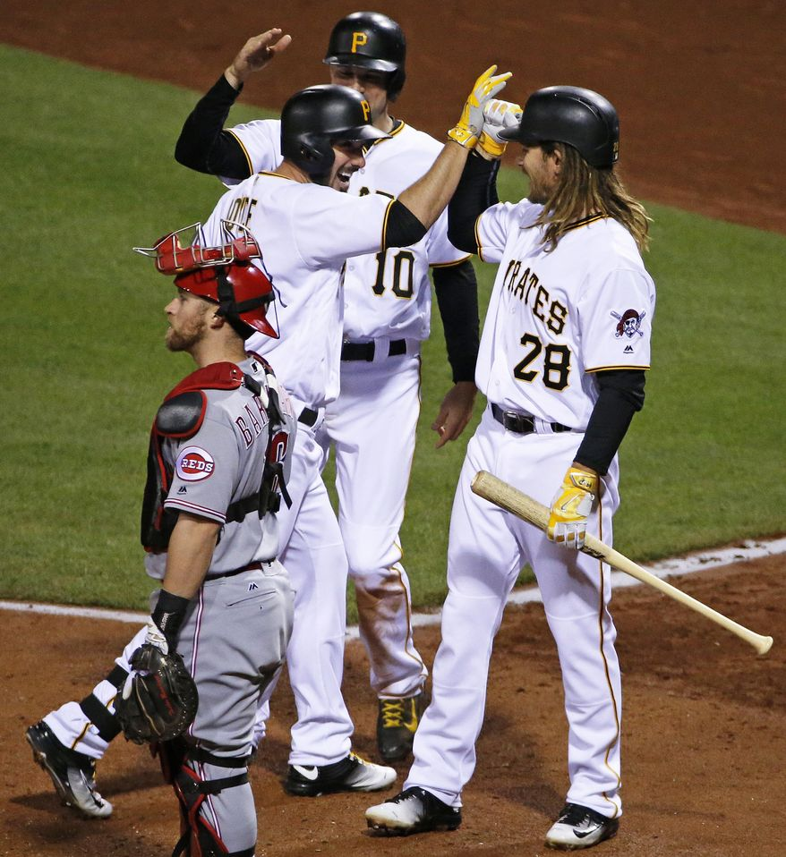Pittsburgh Pirates' Matt Joyce, center, celebrates his two-run home run off Cincinnati Reds relief pitcher J.J. Hoover with teammates Jordy Mercer, rear, and John Jaso (28), next to Cincinnati Reds catcher Tucker Barnhart during the seventh inning of a baseball game in Pittsburgh, Friday, April 29, 2016. (AP Photo/Gene J. Puskar)