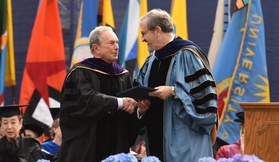 Former New York City Mayor Michael Bloomberg, left, accepts the honorary Doctor of Law degree from University of Michigan President Mark Schlissel, before giving the commencement address, at the University of Michigan's Class of 2016 graduation inside Michigan Stadium on Saturday, April 30, 2016. (Tanya Moutzalias /The Ann Arbor News - MLive.com Detroit via AP)