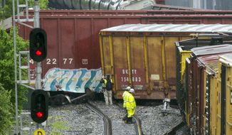 Emergency personnel work at the scene after a CSX freight train derailed, spilling hazardous material, in Washington on Sunday, May 1, 2016. (AP Photo/Cliff Owen)