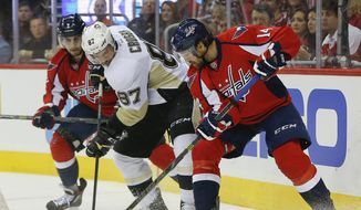 Pittsburgh Penguins center Sidney Crosby (87) goes up against Washington Capitals defenseman Matt Niskanen (2) right wing Justin Williams (14) during the first period of Game 2 in an NHL hockey Stanley Cup Eastern Conference semifinals Saturday, April 30, 2016 in Washington. (AP Photo/Pablo Martinez Monsivais)