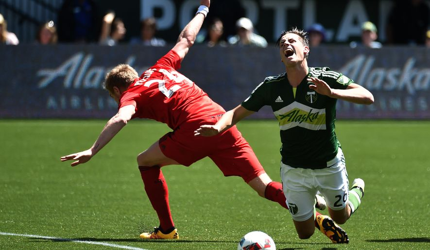 Portland Timbers forward Lucas Melano (26) is tripped by Toronto FC defender Damien Perquis (24) during the first half of an MLS soccer game in Portland, Ore., on Sunday, May 1, 2016.AP Photo/Steve Dykes)