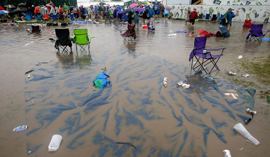The Acura Stage area is flooded after a storm dumped several inches of rain on the second Saturday of the New Orleans Jazz Fest at the Fair Grounds, Saturday, April 30, 2016. (David Grunfeld/NOLA.com The Times-Picayune via AP)