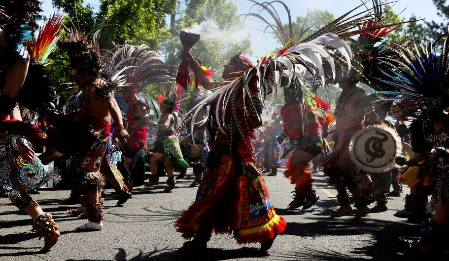 Traditional Aztec dancers headed up the annual El Comite May Day March for Worker and Immigrant Rights, stopping to perform numerous times, Sunday May 1, 2016, in Seattle. (Ken Lambert/The Seattle Times via AP)
