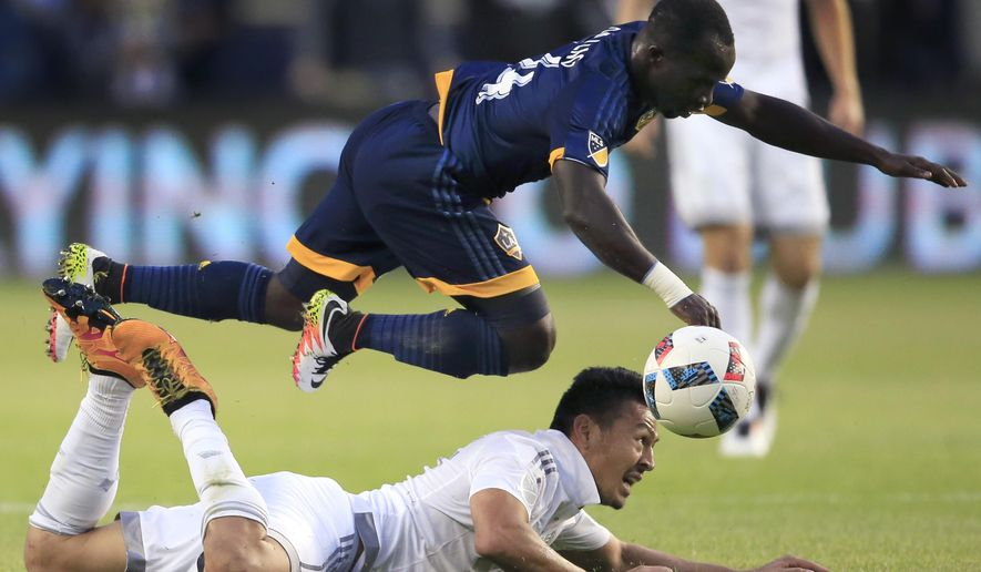 Los Angeles Galaxy midfielder Ema Boateng (24) leaps over Sporting Kansas City midfielder Roger Espinoza, bottom, during the first half of an MLS soccer match in Kansas City, Kan., Sunday, May 1, 2016. (AP Photo/Orlin Wagner)